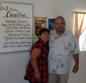 Pastor Leo and Gloria in front of the sign to pray