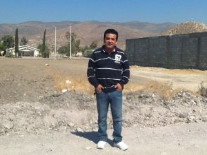 Pastor Ivan Casados with the land for the new church site behind him