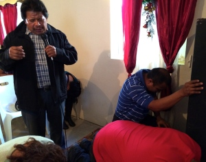 Pastor Eleodoro Rosas praying for those that came up for prayer after the sermon