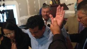 Pastor Daniel praying for Ivan & Rocio during the dedication service