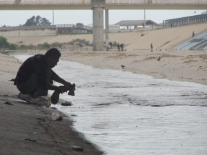 A man washing his clothes in the Tijuana River in El Bordo