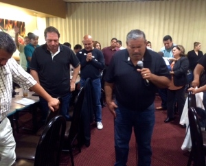 Pastor Daniel Nuñez with the mic leading us in prayer at the pastors meeting for Lo Mejor del Trigo